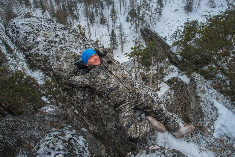 De mensenwandelaar heeft rust bij bergbovenkant, ontspant het liggen op rots royalty-vrije stock foto's
