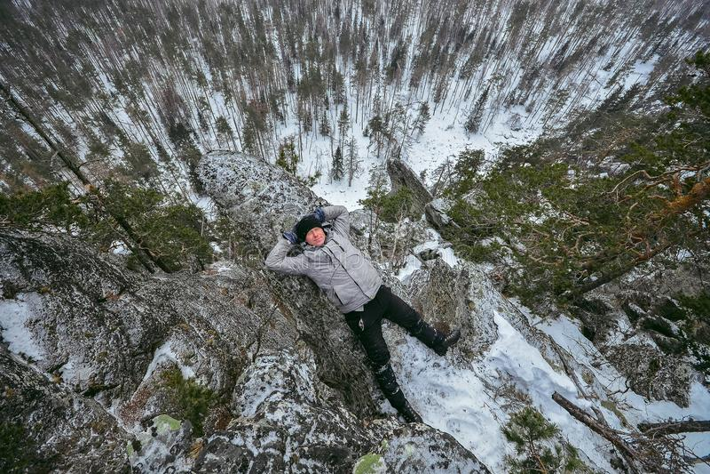 De mensenwandelaar heeft rust bij bergbovenkant, ontspant het liggen op rots royalty-vrije stock foto