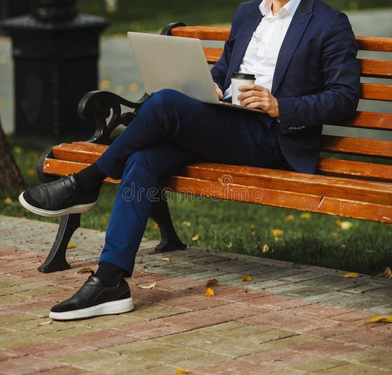 De mensenzitting op bank met laptop en houdt koffie in hand royalty-vrije stock afbeelding