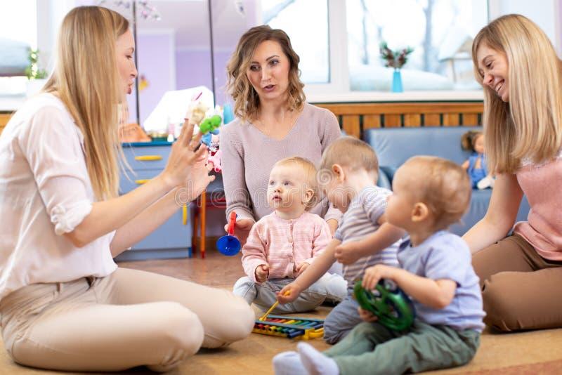 De mentor en 1 jaar de oude babys spelen met onderwijsspeelgoed in kleuterschool of opvangcentrum royalty-vrije stock afbeelding