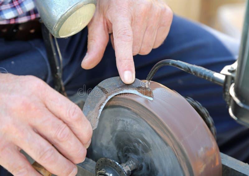 de messenslijper scherpt een rekening-snijder gebruikend een malend wiel royalty-vrije stock afbeelding