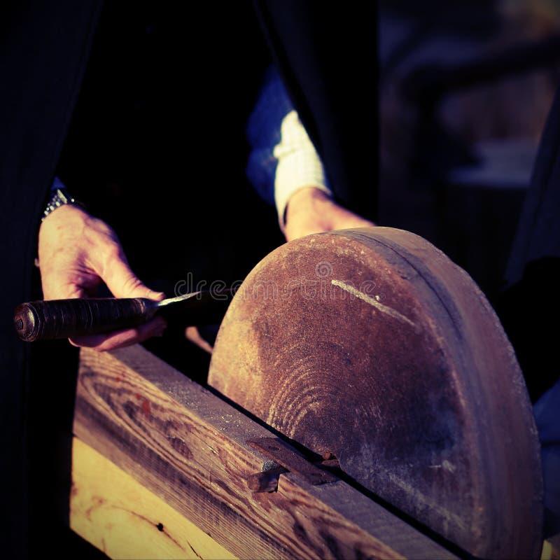 De messenslijper scherpt zijn mes met uitstekend effect stock afbeeldingen