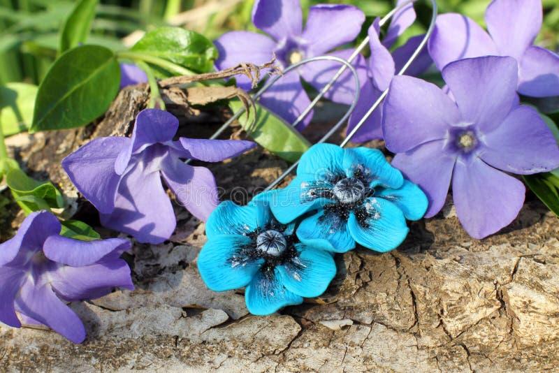 De met de hand gemaakte blauwe oorringen van de bloemklei op de aardachtergrond stock foto's