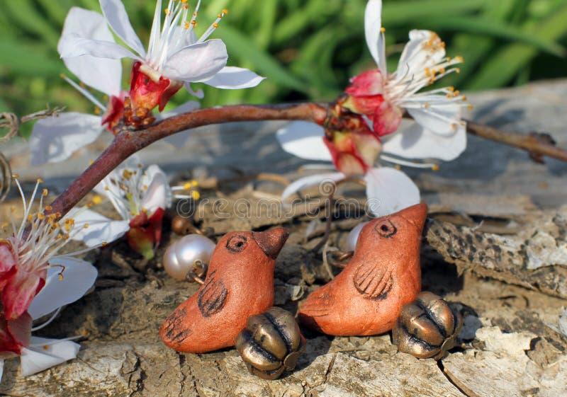 De met de hand gemaakte oorringen van de kleivogel op de aardachtergrond stock foto