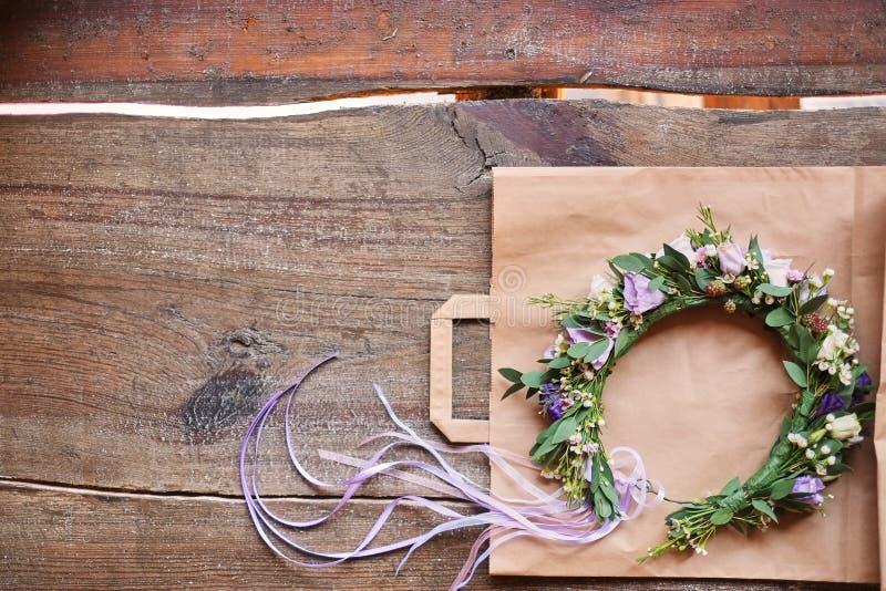 De met de hand gemaakte bloemendietiara van bloemen wordt gemaakt ligt op houten achtergrond Modieuze hand - gemaakte kroon van b royalty-vrije stock foto