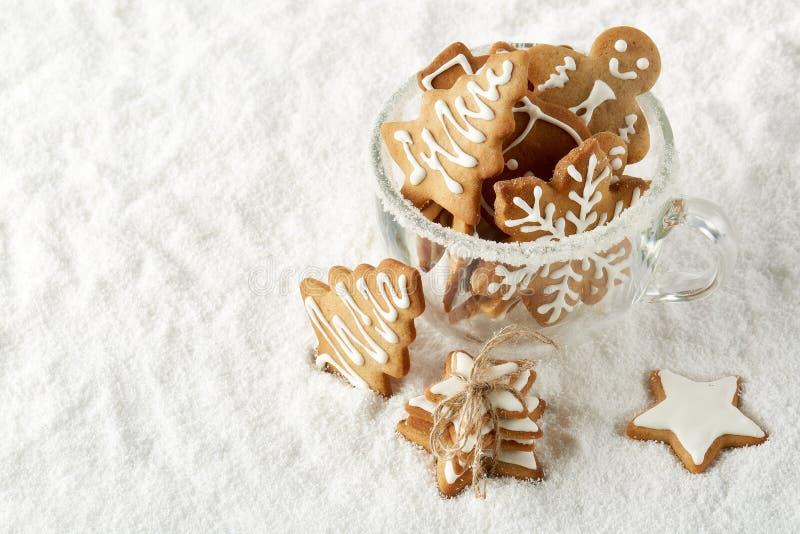 De met de hand gemaakte koekjes in een glas vormen status op de witte achtergrond van de de wintersneeuw met exemplaarruimte tot  stock afbeeldingen
