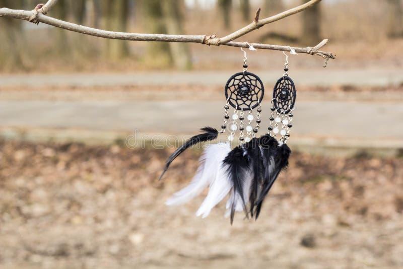 De met de hand gemaakte vanger van de oorringendroom met veren past en parelt kabel het hangen in royalty-vrije stock afbeelding