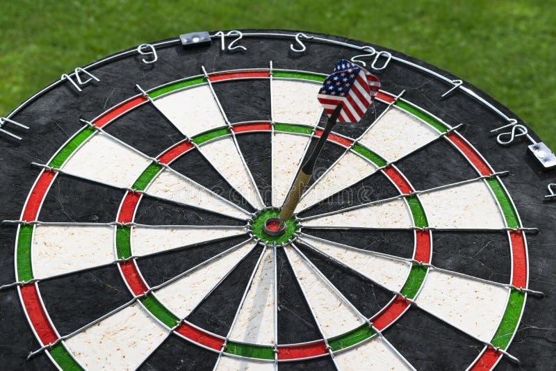 De metaalpijltjes hebben rode bullseye op een dartboard geraakt Het spel van pijltjes De pijltjespijl in de pijltjes van het doel stock foto