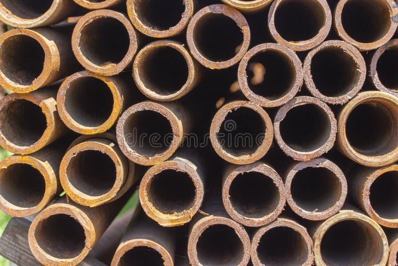 De metaalpijpen van ijzer met sporen van roest worden gemaakt, bouwmaterialen, de achtergrondtextuur die is horizontaal Ronde roe royalty-vrije stock foto's