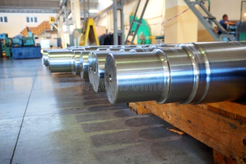 De metaalproducten in het pakhuis, grote ronde schachten liggen op een houten rek in de fabriek in de winkel royalty-vrije stock fotografie