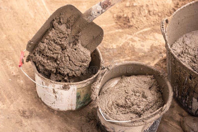 De metselaar kneedt cementmortier voor het gieten van concrete screed royalty-vrije stock foto