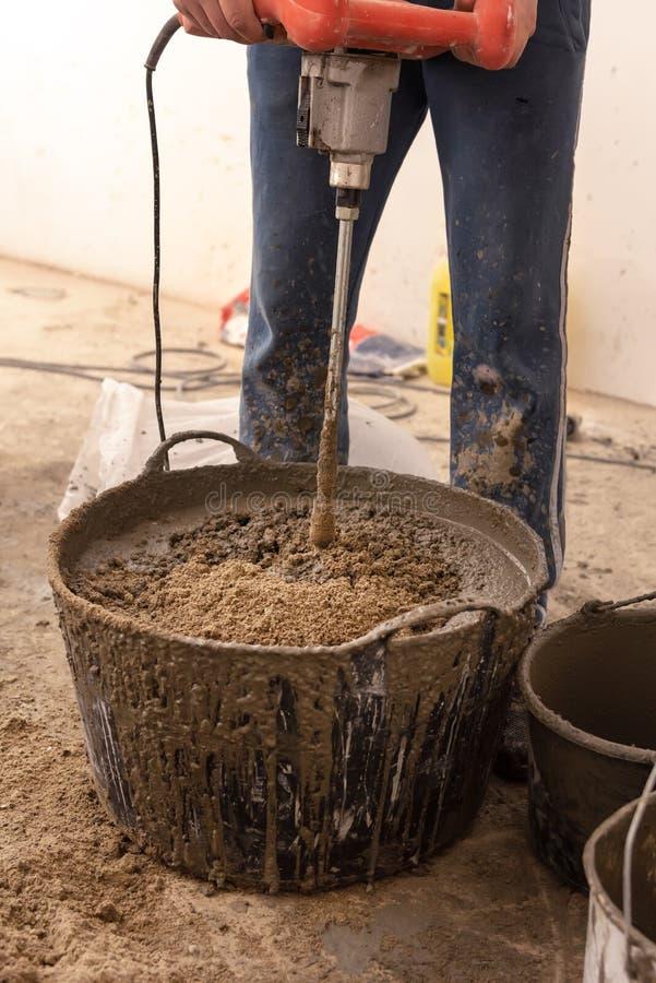 De metselaar kneedt cementmortier voor het gieten van concrete screed stock fotografie