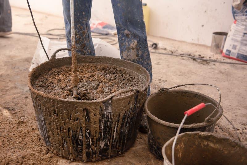 De metselaar kneedt cementmortier voor het gieten van concrete screed stock foto