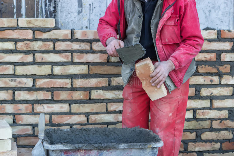 De metselaarhand spreidde een mortier op baksteen uit stock afbeelding