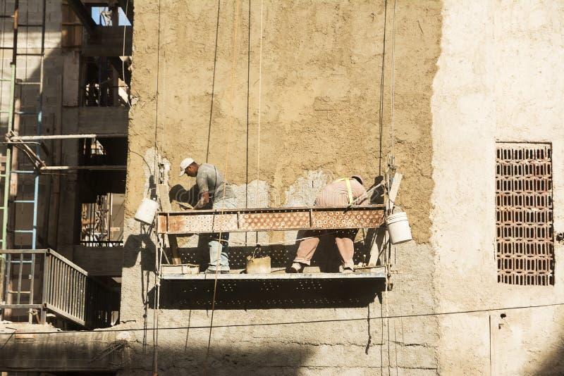 De metselaars werken aan de wederopbouw van een gebouw in het centrum van stock foto's