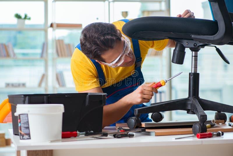 De meubilairhersteller die bij het herstellen van de stoel werken stock foto's