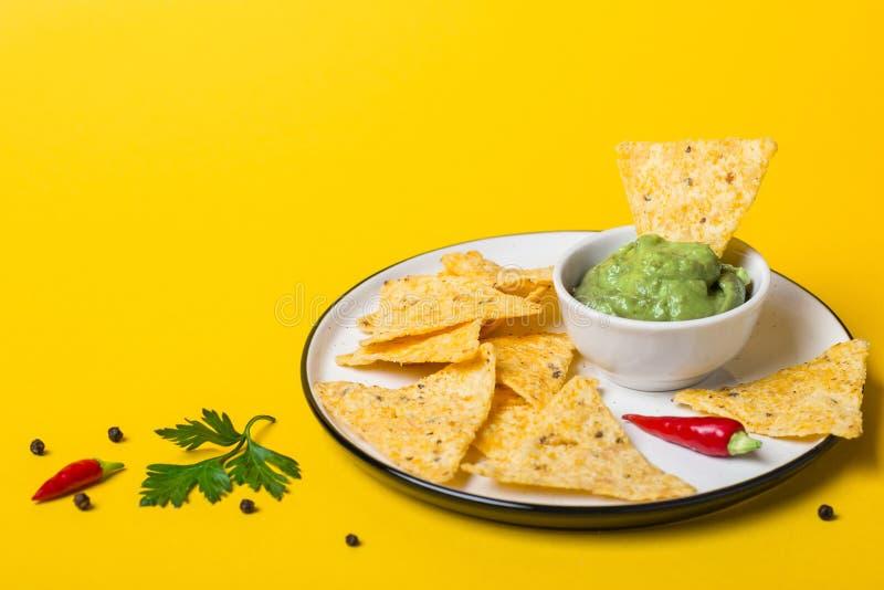De Mexicaanse onderdompeling van voedselguacamole met Graanspaanders op gele achtergrond stock fotografie