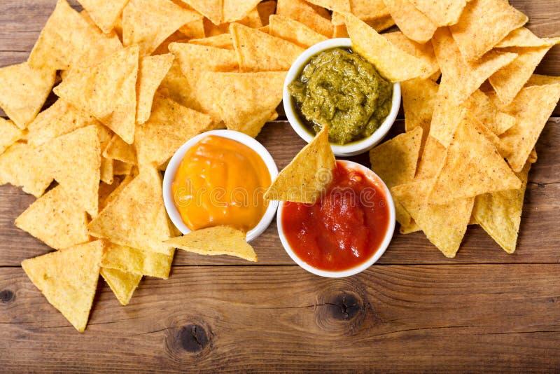 De Mexicaanse spaanders van het nachosgraan met guacamole, salsa en kaasonderdompeling stock foto's