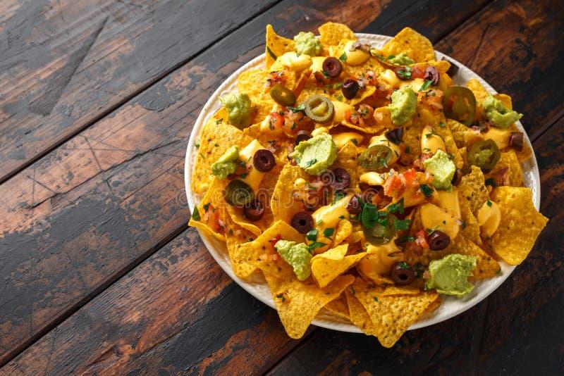 De Mexicaanse spaanders van de nachostortilla met olijven, jalapeno, guacamole, tomatensalsa en kaasonderdompeling royalty-vrije stock foto
