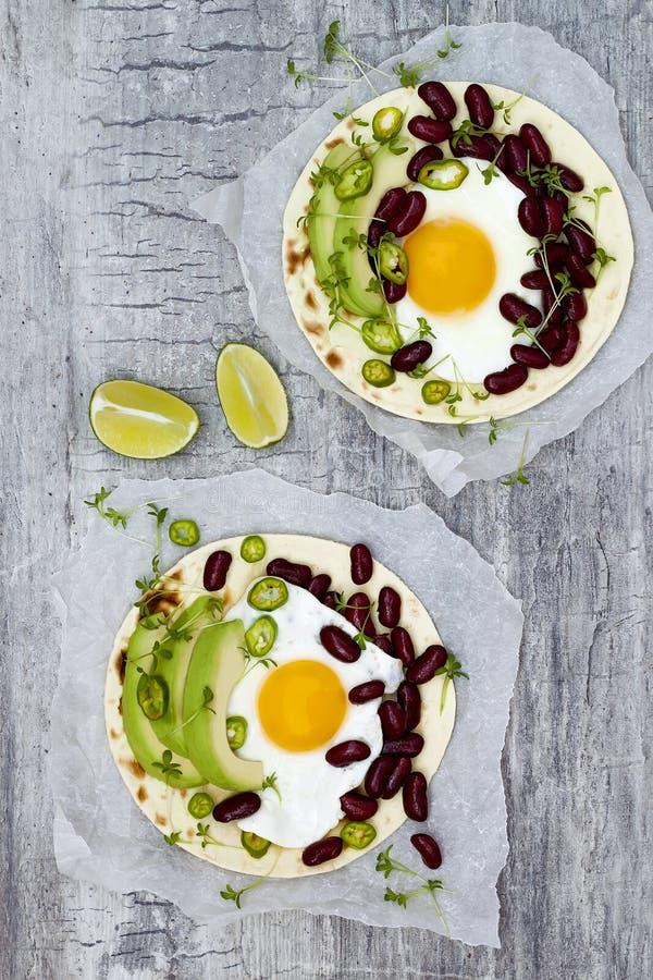 De Mexicaanse taco's van huevosrancheros Ontbijttostadas met zwarte bonen, avocado, braadden ei, microgreens, srirachaketchup Hoo stock foto