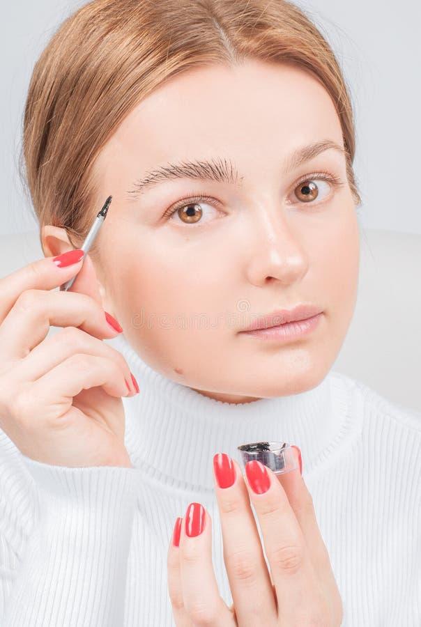 De Microbladingswenkbrauwen, vrouw past verfhenna op wenkbrauwen toe Professionele wenkbrauwzorg, het verven en permanente samens stock foto
