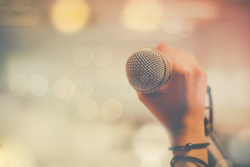 De microfoon van de handholding en bokeh achtergrond, concept als muziekinstrument in studioruimte stock afbeeldingen