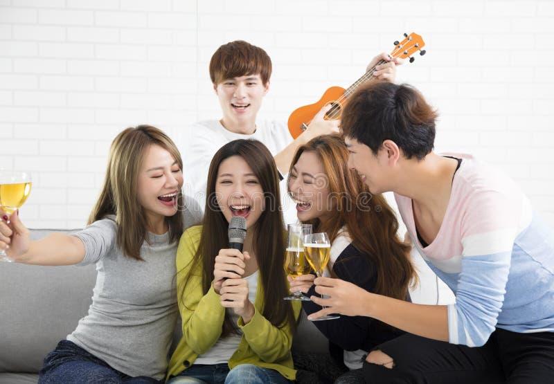De microfoon van de vrouwenholding en het zingen bij karaoke stock fotografie