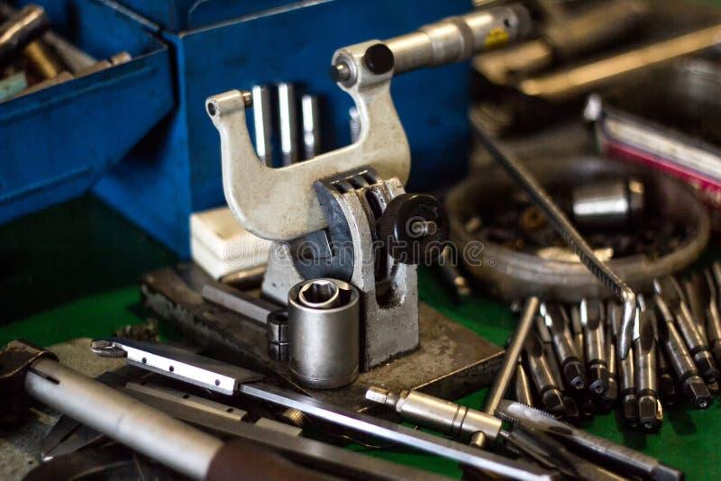 De micrometer en andere hulpmiddelen om metaal te boren en te snijden liggen op de lijst, close-up, productie stock afbeeldingen