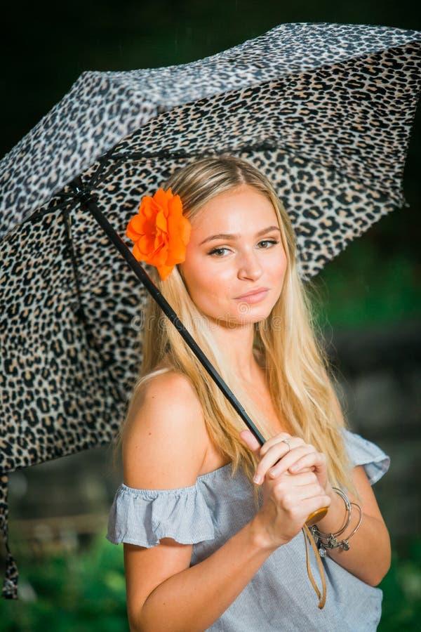 De middelbare schooloudste stelt met paraplu voor portretten op regenachtig royalty-vrije stock fotografie