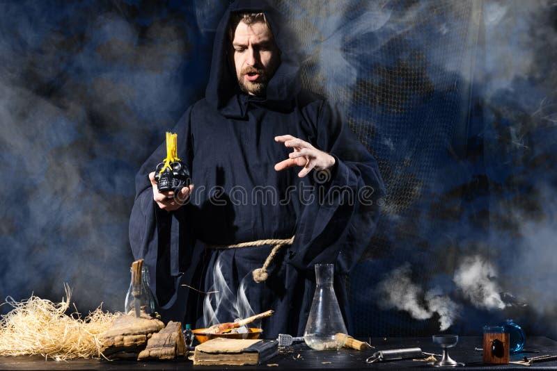 De middeleeuwse alchimist maakt magisch ritueel bij de lijst in zijn rooklaboratorium royalty-vrije stock fotografie