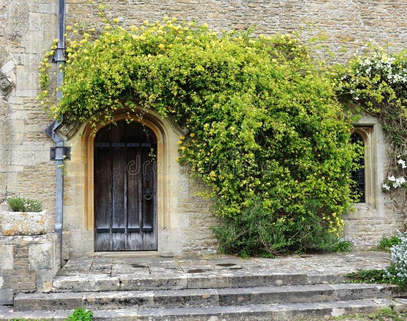 Download De Middeleeuwse Bouw Met Houten Deur Stock Afbeelding - Afbeelding bestaande uit middeleeuws, bloemen: 54082833