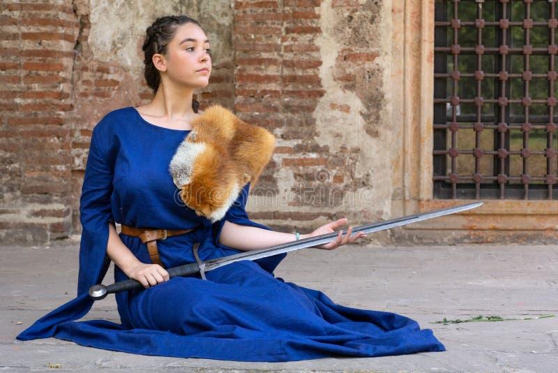 De middeleeuwse dame in een blauwe kleding met vosbont op schouder houdt een zwaard in haar handen en zit op de vloer stock foto's