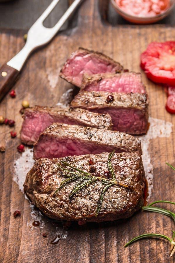 De middelgrote zeldzame geroosterde plakken van het rundvleeslapje vlees op rustieke houten achtergrond, sluiten omhoog stock foto's
