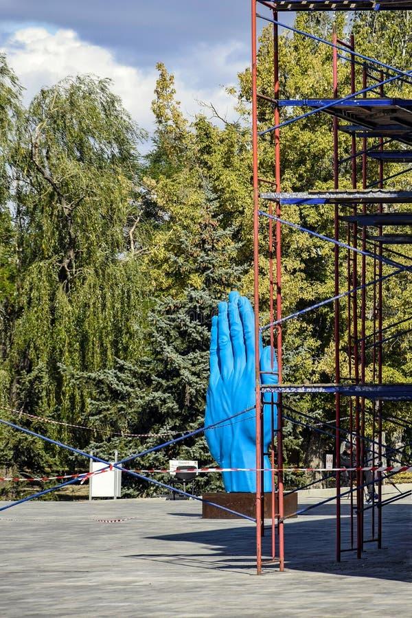 De middelste-wegsculptuur Nikolaev, Oekraïne Kunstobjecten in de vorm van een enorme blauwe hand - symbool dat vriendschap beteke stock afbeeldingen