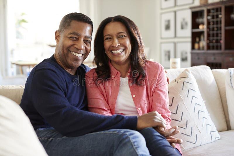 De midden oude Afrikaanse Amerikaanse paarzitting op de bank in hun woonkamer die aan camera, vooraanzicht kijken, sluit omhoog royalty-vrije stock fotografie