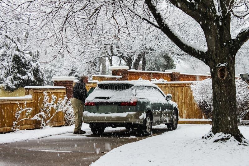 De midden oude mens met sneeuw behandelde auto in oprijlaan op uiterst sneeuwdag met sneeuw het vallen stock foto's
