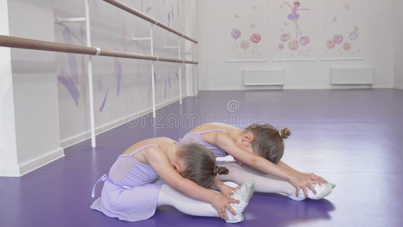De mignons petits ballerines s'étirent ensemble à l'école de danse photo libre de droits