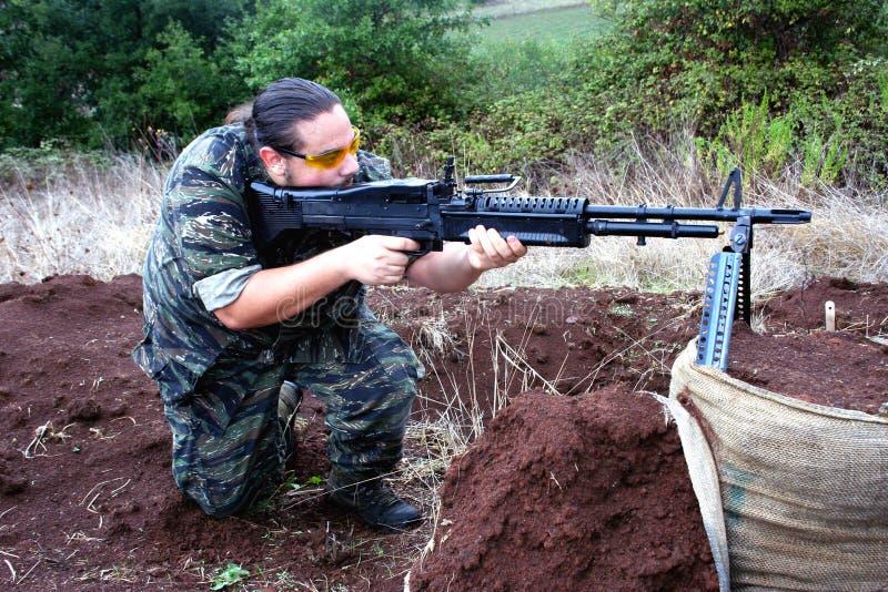 De militair die van Airsoft met M60 ontspruit stock afbeeldingen
