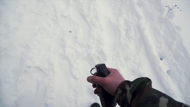 De militair houdt in zijn hand een opleidingsgranaat terwijl het overgaan van militaire oefeningen in het leger, sneeuwachtergron royalty-vrije stock foto's