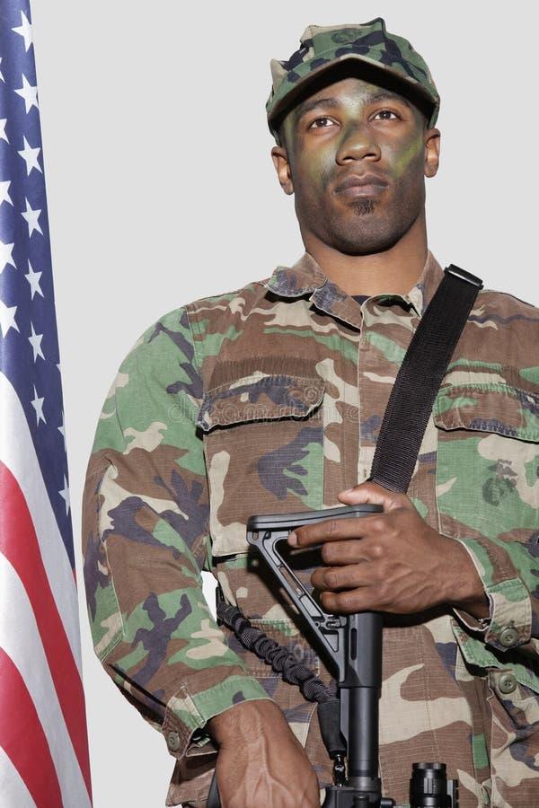 De militair van de V.S. Marine Corps met M4 aanvalsgeweer die zich door Amerikaanse vlag over grijze achtergrond bevinden stock foto