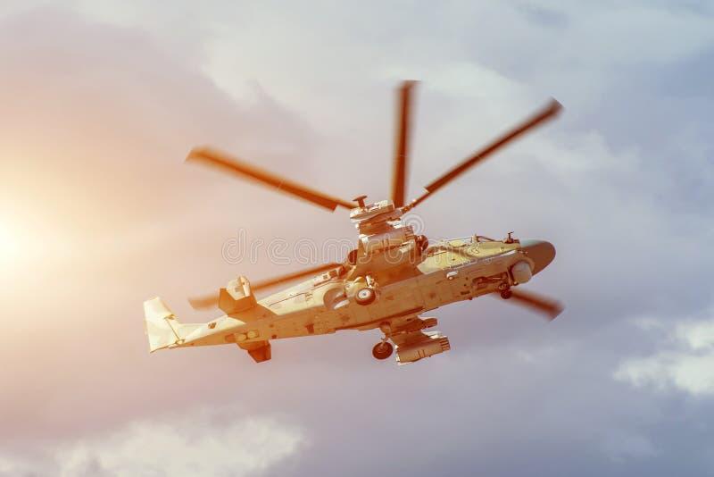 De militaire gevechtshelikopter vliegt snel het draaien in de lucht stock foto