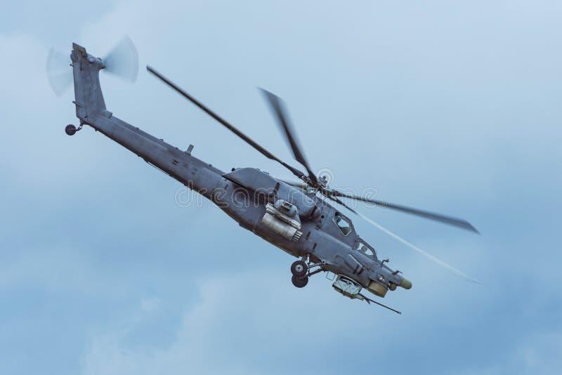 De militaire gevechtshelikopter vliegt snel het draaien in de lucht stock afbeeldingen