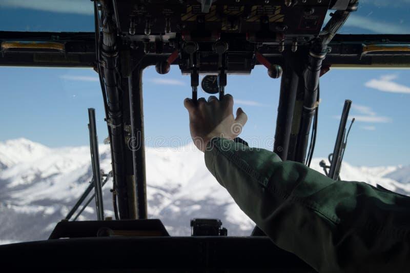 De militaire helikopter die door wit vliegen sneeuwde bergen stock foto