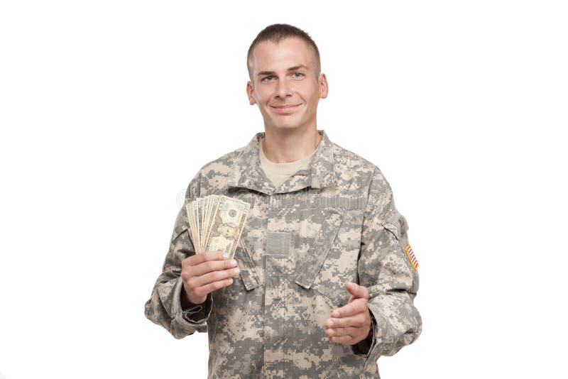 De militair met geld breidt zijn hand uit stock afbeelding
