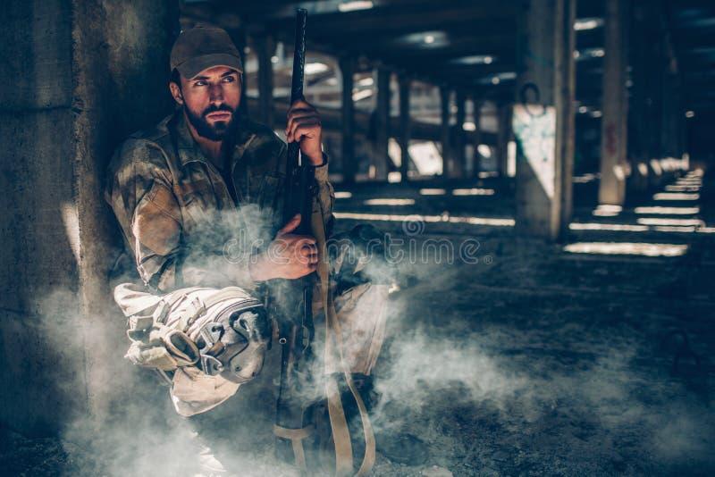 De militaire mens zit achter kolom en houdt geweer dicht bij zijn lichaam Hij zit zeer stil De kerel wacht Hij royalty-vrije stock foto