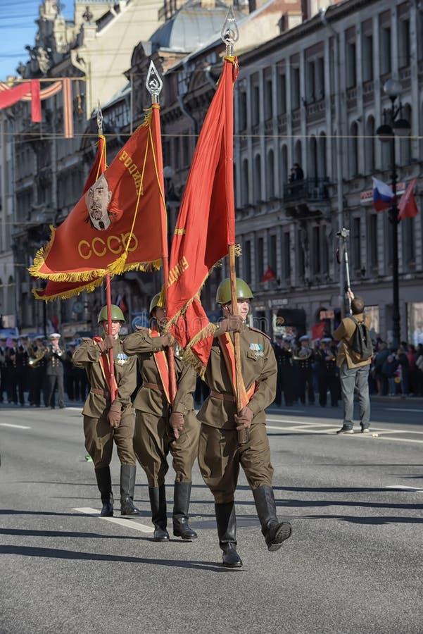 De militairen in de vorm van de Tweede Wereldoorlog met de Sovjetvlaggen in hun handen bij de overwinning paraderen royalty-vrije stock fotografie