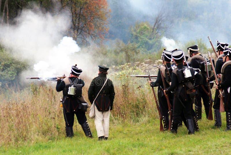 De militairen schieten met kanonnen stock afbeelding