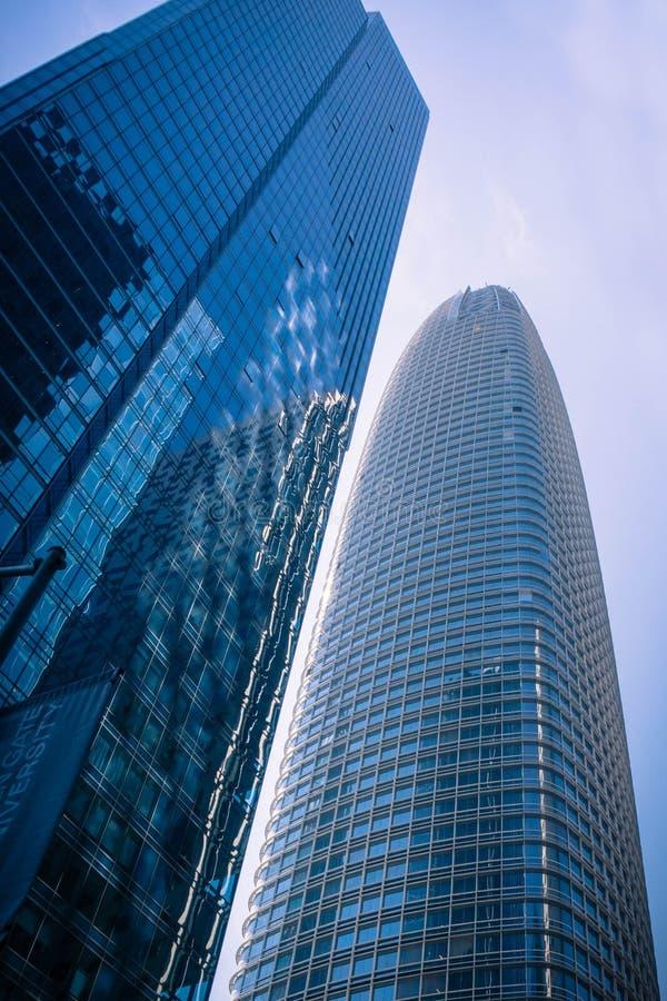 De millenniumtoren blijft langzaam naar de nieuwe Salesforce-toren dalen en overhellen stock afbeelding