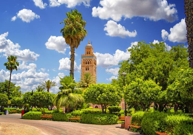 De minaret van de Koutoubiamoskee bij medinakwart van Marrakech, Marokko Er is mooie groene tuin met palmen De blauwe hemel is in royalty-vrije stock fotografie