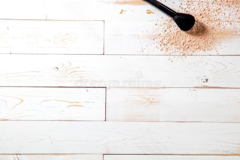 De mineralen van de kunstenaarsstichting en make-upborstel op witte houten achtergrond stock fotografie
